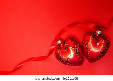 Couple of glass hearts on red ribbon