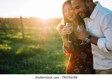 Couple with a glass of wine and enjoying each others company.  Man and woman with a drink and having fun at vineyard.