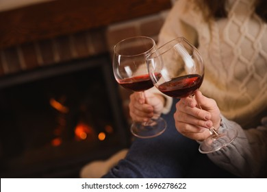 Couple with glasses of red wine near fireplace, closeup