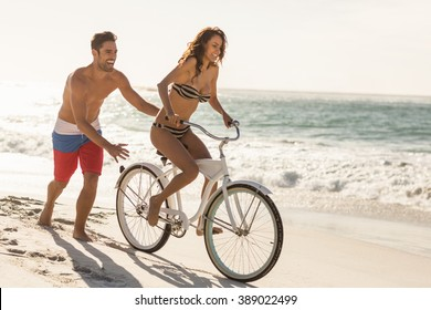 Couple going on a bike ride on the beach on a sunny day