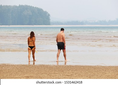 Couple going to swim in the tropical blue sea, colorful landscape. Woman in bikini and man in shorts walk together with goggles for diving, romantic leisure and sandy beach vacation