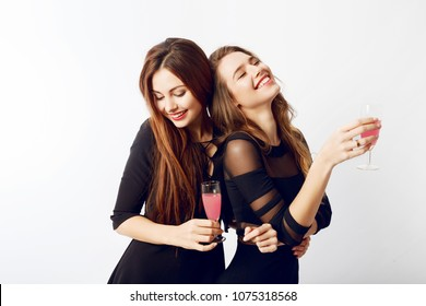 Couple of graceful woman in stylish black party dress spending great time together , drinking cocktails , having fun. White background. Flash portrait.