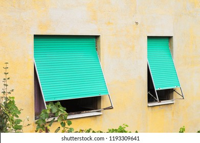 A couple of green windows of a yellow house (Marche, Italy, Europe)
