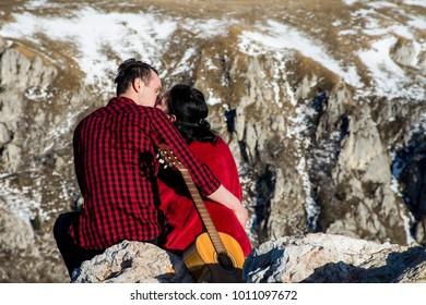 Couple with a guitar on a rocky mountain