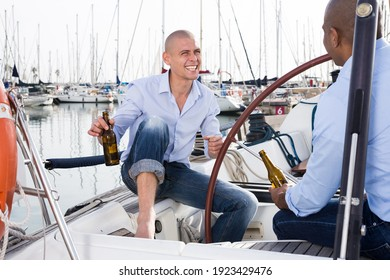 A couple of guys in blue shirts and jeans chatting on a private yacht in the port