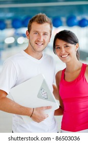 Couple at the gym holding a scale - lose weight concepts