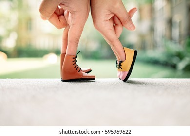 Couple hand finger walk to kiss with shoe concept, Feet of the kissing couple