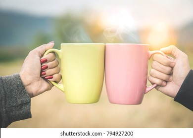 couple hands clink hot coffee mug outdoor  in the morning , friends enjoy drinking together cheers for two cup