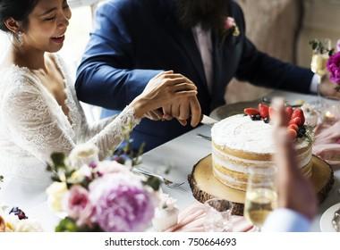 Couple Hands Cutting Wedding Cake