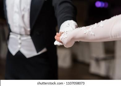 Couple hands dancing waltz at ball