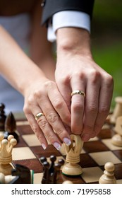 A couple hands hold a chess pieces