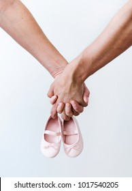 Couple hands holding baby girl shoes