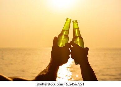 Couple hands holding beer bottles clanging and celebrating on holiday at the beach in summer sunset