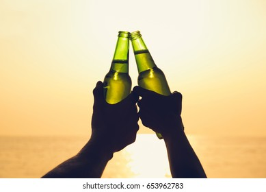 Couple hands holding beer bottles and clanging, celebrating on holiday at the beach in summer sunset
