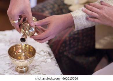 Couple hands holding Buddhist's grail pouring water from gold gourds filled with holy water for use in Buddhist ceremonies