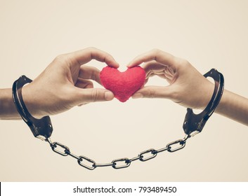 A couple' hands holding as a red heart together with hand cuffs / Love and romance on Valentine's day concept