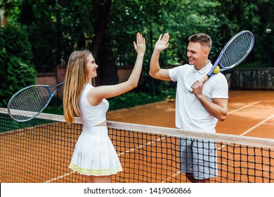 Couple handshaking at the tennis court after playing a game..