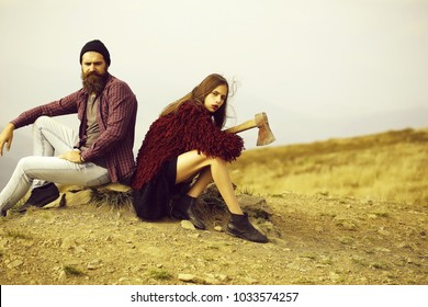 Couple of handsome bearded hipster in checkered shirt and pretty cute sexy young fashion girl or woman sitting on stone with ax on mountain top on natural background