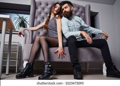 Couple of handsome bearded hipster in jeans shirt and pretty cute sexy young fashion girl or woman sitting on couch. young stylish hipster couple in love, embrace, cool accessories, happy, long beard