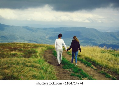 Couple of handsome bearded man in white shirt and pretty young cute girl or woman in black hoody holding hands and walking on meadow road on blue sky background.