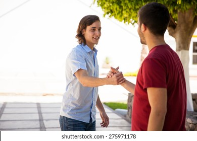 Couple of handsome male friends greeting with a handshake at school. Lots of copy space