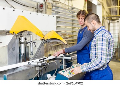 A couple of happy adult men working around the milling machine at factory