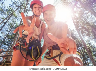 Couple of happy climbers having fun in adventure park outdoor - Young friends doing extreme sport - Travel,wanderlust and summer vacation - Focus on faces - Warm filter with back sun light