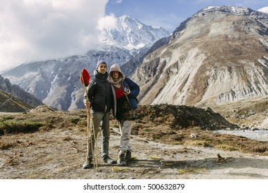 A couple of happy europeans posing for the photo on the trail in the mountains. Tilicho lake base camp, Annapurna Conservation Area, Himalayas, Nepal.