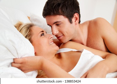 couple has fun in bed. laughter, joy and eroticism in the bedroom