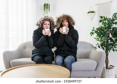 A Couple have cold on the sofa at home with winter coat