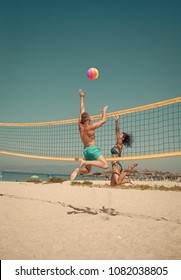 Couple have fun playing volleyball. Young sporty active couple beat off volley ball, play game on summer day. Woman and man fit, strong, healthy, doing sport on beach. Beach volleyball concept.