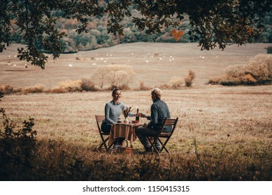 Couple have lunch in nature. Table set in autumn nature
