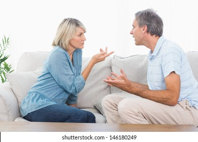 Couple having an argument at home on couch