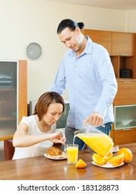 couple having breakfast with juice in morning at home