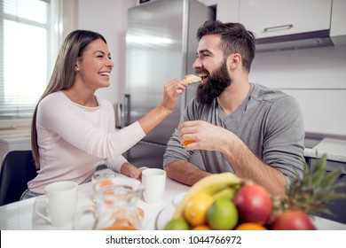 Couple having breakfast in the morning.Girl feeding her boy with a piece of croissant.