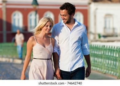 Couple having a city break in summer walking in the evening light