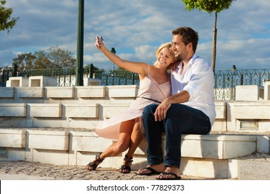 Couple having a city break in summer sitting on a brick wall in the sunlight, making pictures
