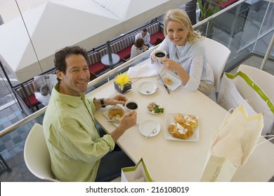 Couple having coffee in cafe, smiling, portrait, elevated view