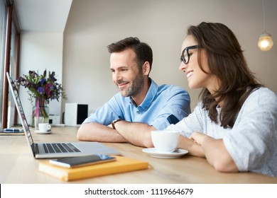 Couple having coffee in cafe together and looking at laptop