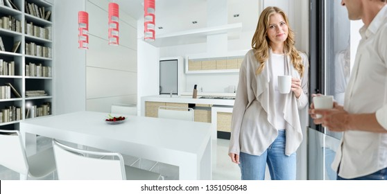 Couple having a coffee in a house with a modern open  plan kitchen