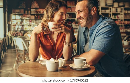 Couple having coffee at a coffee shop. Man and woman meeting at cafe.