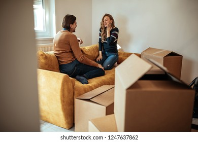 Couple having conversation while they are moving into new apartment