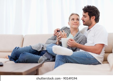 Couple having a cup of coffee in their living room