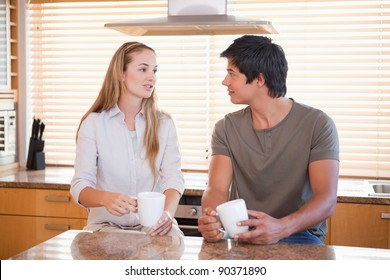 Couple having a cup of coffee in their kitchen