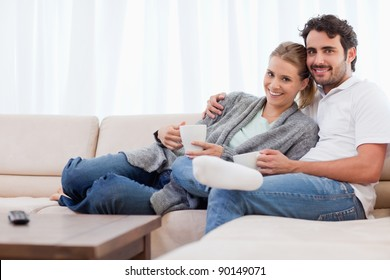 Couple having a cup of tea in their living room