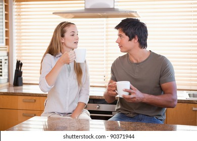 Couple having a cup of tea in their kitchen