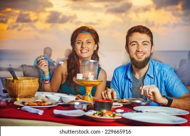 A couple having dinner on the Jimbaran beach in Bali (looking at camera)