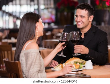 Couple having dinner at a restaurant and making a toast