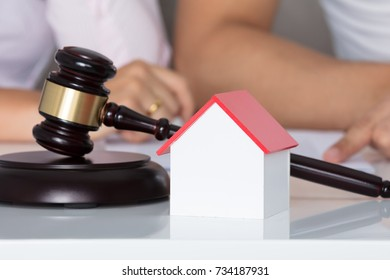 Couple Having Discussion Over Property After Divorce Behind House Model And Gavel