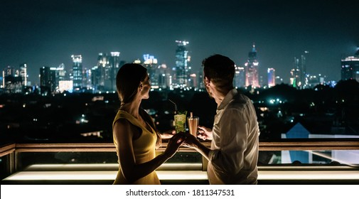 couple having a drink on roof terrace overlooking the city skyline